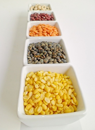Mung bean, black-eyed pea, red adzuki bean, red lentil, and green lentil in white bowls arranged in a row Stock Photo