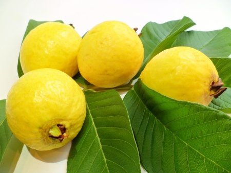 guava: Exotic yellow guava from Hawaii with greeen leaves on white background