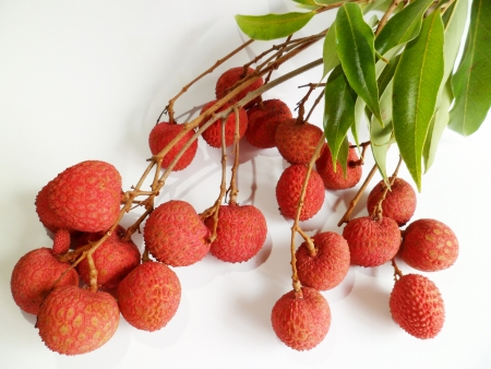 greeen: Bunch of fresh lychee from Hawaii with greeen leaves on white background Stock Photo