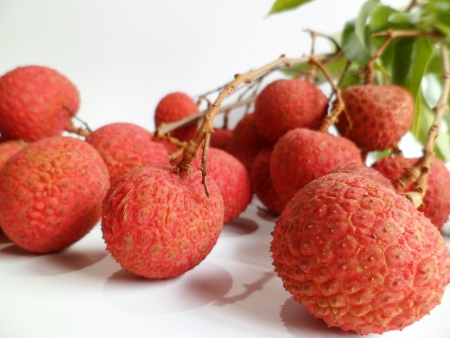 greeen: Close-up of fresh lychee fruits  from Hawaii with greeen leaves on white background