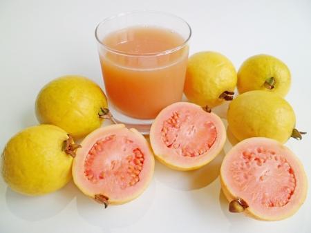 guayaba: Un vaso de jugo de guayaba y frutos de guayaba de Hawai en el fondo blanco