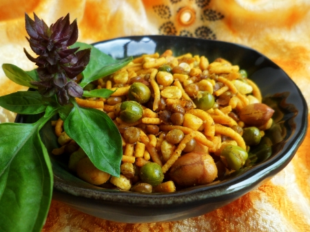 Indian savory snack arranged in a bowl with orange sari cloth in background