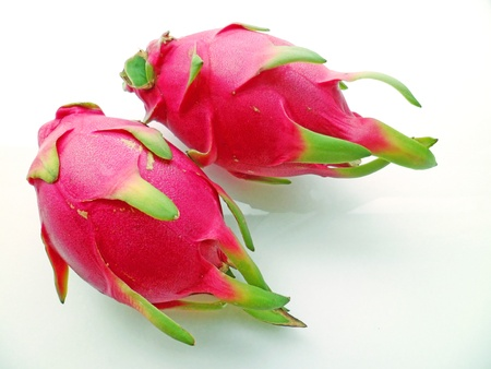 Two red dragonfruits arranged side by side on white background photo