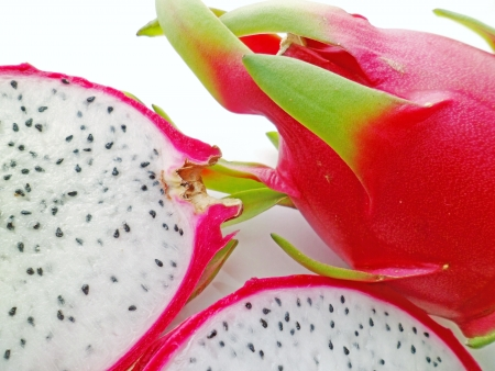 enzyme: A red dragonfruit with two cut slices arranged side by side on white background Stock Photo