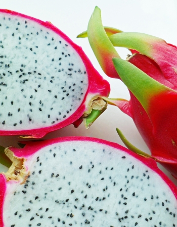 enzyme: A red dragonfruits with two cut slices arranged side by side on white background