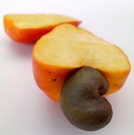 Cashew apple cut open on white background