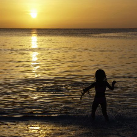 mile: Golden Caribbean Sunset with Silhouette of Child from Seven Mile Beach, Grand Cayman