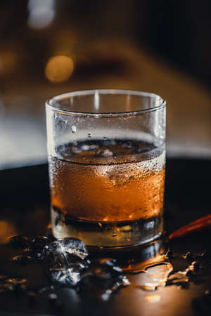 Refreshing alcoholic cocktail. Whiskey and coke. Ice in a glass, mixing ingredients.