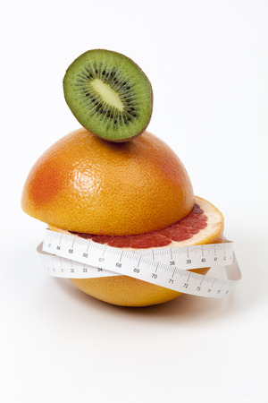 Half sliced red grapefruit and kiwi and tape measure wrapped around. Image is over white background.