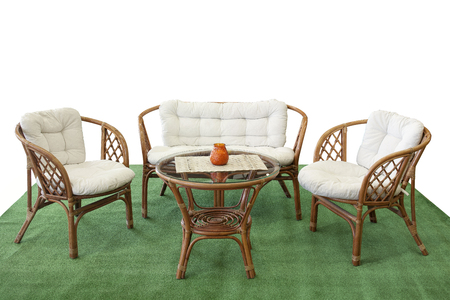 Set of garden furniture from rattan with pillows on artificial grass. Isolated with clipping path.