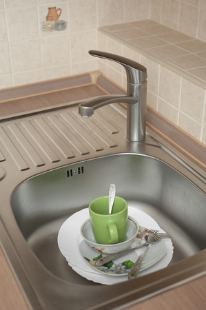 Wash the dishes in the metal sink in the kitchen photo