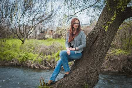 Young woman with glass sit o the tree photo