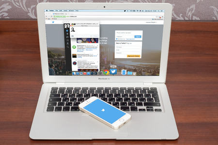 Pavlograd, UKRAINE - December 18 2014: brand new Apple iPhone 5S with Twitter logo on the screen and twitter page on laptop. Twitter is a social media online service for microblogging and networking communication.