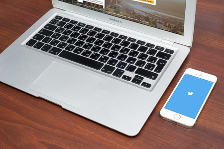 Pavlograd, UKRAINE - December 18 2014: brand new Apple iPhone 5S with Twitter logo on the screen and twitter page on laptop. Twitter is a social media online service for microblogging and networking communication. Editorial