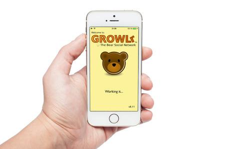 homosexuales: Pavlograd, Ucrania- 22 de diciembre 2014: La foto de una mano usando GROWLr aplicaci�n en el iPhone 5S. GROWLr es la aplicaci�n completa de redes sociales para los homosexuales Editorial