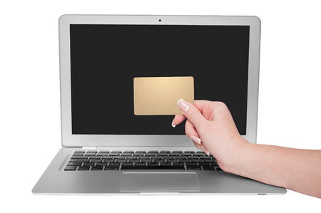 debet: Woman holding gold credit card in hand. On-line shopping on the internet using a laptop. Editorial