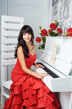 sumptuous: Young beautiful woman in a red evening dress sits at the piano. Looking at the camera