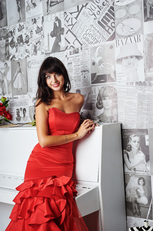 red evening: Young beautiful woman in a red evening dress near piano Stock Photo