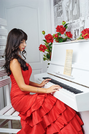 sumptuous: Young beautiful woman in a red evening dress sits at the piano