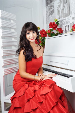 red evening: Young beautiful woman in a red evening dress sits at the piano