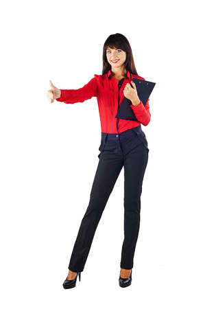 Young beautiful Caucasian business woman in red t-shirt holding clipboard and show thumbs up. Isolated in full length on white background Stock Photo