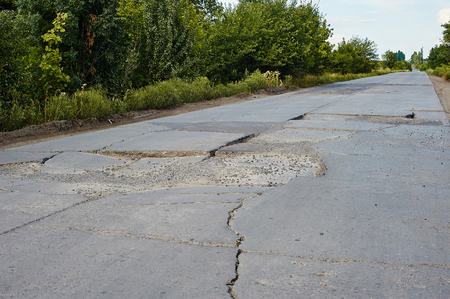 winter thaw: Damaged asphalt pavement road with potholes caused by freeze and thaw cycle during winter. Damaged asphalt in Ukraine.