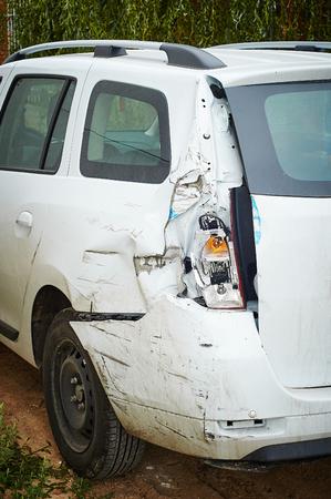 fender bender: White car after an accident. Broken car headlight and rear bumper.