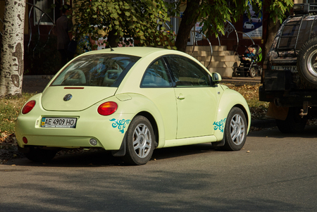 mini car: Krivoy Rog, Ukraine - September 24, 2015: Light green Volkswagen New Beetle car parked in a street of the city centre.