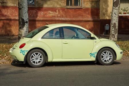 escarabajo: Krivoy Rog, Ucrania - 24 septiembre, 2015: Volkswagen New Beetle verde claro aparcado en una calle del centro de la ciudad. Editorial