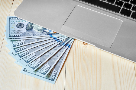 trackpad: Laptop keyboard with dollars on a wooden background. Silver metal laptop with trackpad.
