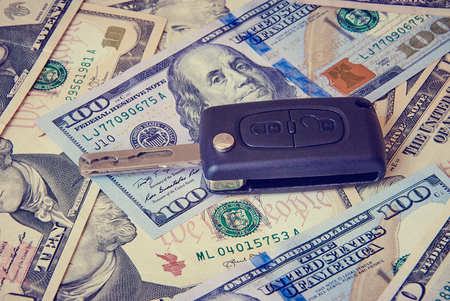 keyless: Car key on a background of dollars. Business concept. Toned image