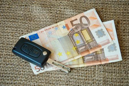 keyless: Money and car keys on a burlap background.