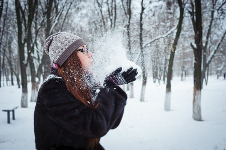winter: Beauty Winter Girl Blowing Snow in frosty winter Park. Flying Snowflakes.  Joyful Beauty young redhead woman Having Fun in Winter Park