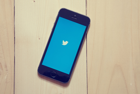 enables: KRIVOY ROG, UKRAINE - OCTOBER 20, 2015: iPhone 5s with Twitter app on wooden background. Twitter is an online social networking and microblogging service that enables users to send and read tweets, limited to 140 characters.