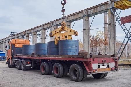 unloading: Cranes unloading a freight transport with still rolls Editorial