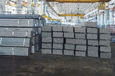 pipe water pipeline: Metal pipes in a warehouse. Stacks of new square steel pipe in factory. Stock Photo