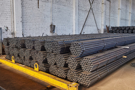 Metal pipes in a warehouse. Stacks of new round steel pipe in factory.