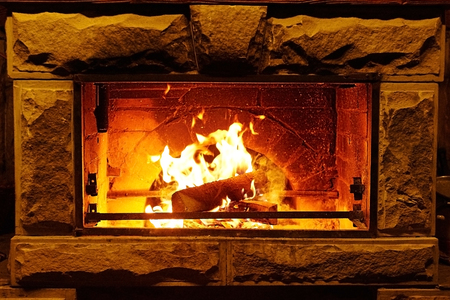 coziness: Bright flame of fire burns in old fireplace Stock Photo
