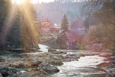 solar flare: Mountain river and wooden house in mountains. Sunny day, solar flare Stock Photo