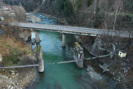 full suspended: Highway and damaged pedestrian suspension bridge across mountain river (view from above) in Yaremche, Ukraine