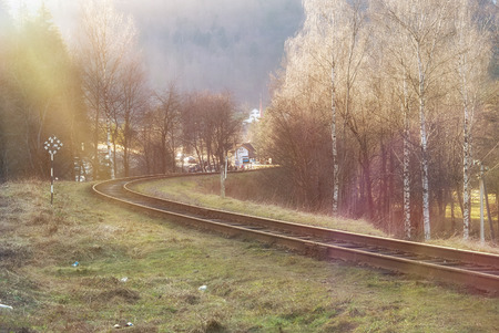 outskirts: Landscape of railroad tracks across rural countryside along outskirts of a village. Sunny day. Solar flare