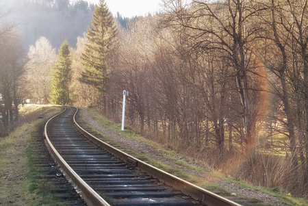 solar flare: Landscape of railroad tracks across rural countryside along outskirts of a village. Sunny day. Solar flare