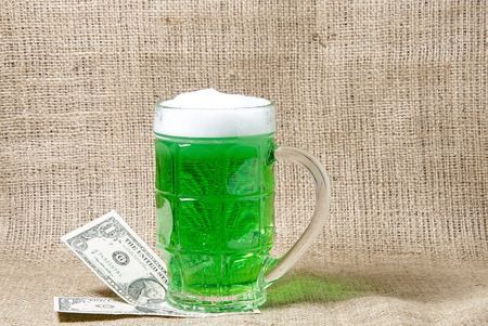cash: Glass of Irish green beer and dollars on a burlap background. Traditional symbols of St. Patricks day. Place for text