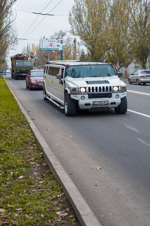 snob: Donetsk, Ukraine - October 22, 2013: White Hummer H2 limousine at the city street. Editorial