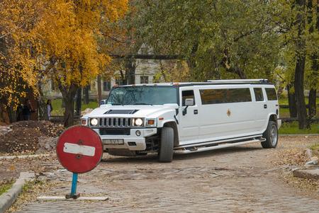 pretentious: Donetsk, Ukraine - October 22, 2013: White Hummer H2 limousine at the rural street.