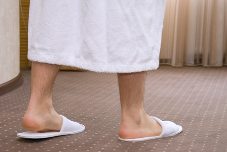 house robe: Young man legs with white bathrobe and slippers on carpet Stock Photo