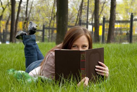 beautiful redhead: Beautiful redhead woman hiding behind the book in park