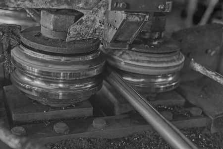 Rolling forming rolls metal works on manufacture of pipes. Rolling mill machine for rolling steel sheet. Black and white image