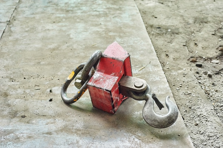 hook up: Red Industrial hook on concrete floor. Close up image
