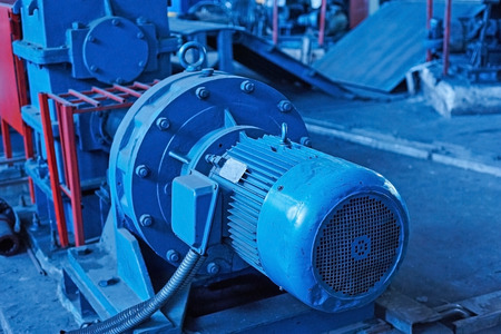 gudgeon: Electric actuator for industrial mill in workshop. Close up. Cold toned image